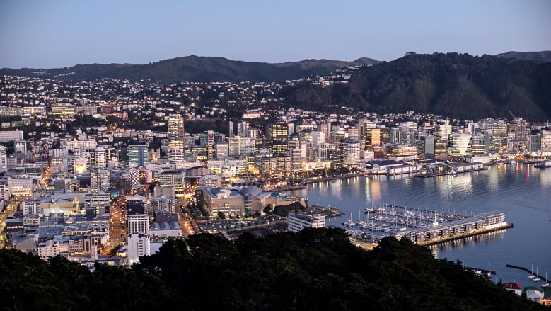 Buildings stand illuminated at dawn in Wellington, New Zealand.