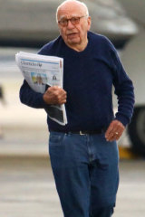 Rupert Murdoch, clutching copies of Fairfax Media's Sydney Morning Herald and Australian Financial Review, stretches his legs at Sydney Airport as his jet is refuelled.
