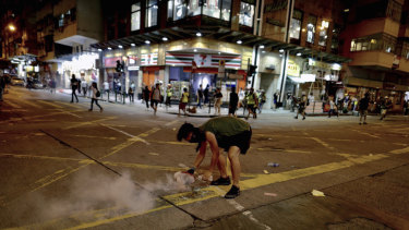 A protester uses a plate to cover a tear gas during clashes with policemen near the Shum Shui Po police station in Hong Kong.