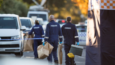 Police carry bags of evidence on Thursday morning.