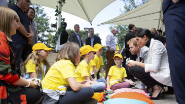 Britain's Prince Harry and his wife Meghan, the Duchess of Sussex meet children from Australian Kookaburra Kids Foundation while attending a lunchtime Reception hosted by Australian Prime Minister Scott Morrison with Invictus Games competitors and representatives of the community in the city's central parkland, The Domain (
