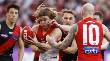 Crowded: James Rowbottom of the Swans, playing in just his fifth game, is tackled by Dylan Clarke at the MCG.