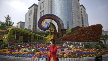 A woman walks by a display in the shape of a train and a container vessel for promoting the Belt and Road Forum in Beijing.