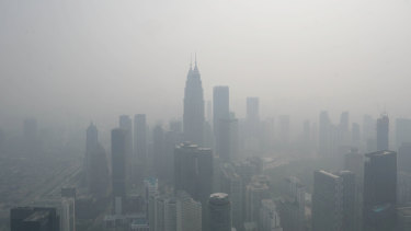 The Petronas Twin Towers, centre, and other buildings stand shrouded in haze in Kuala Lumpur, Malaysia.