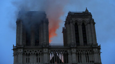 Smoke and flames fill the sky as a fire burns at the Notre-Dame Cathedral during a visit by French President Emmanuel Macron in Paris.
