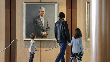Brisbane's Bernard Macnaught and his children Thomas and Victoria view former prime minister Bob Hawke's portrait during their visit to Parliament House last week.