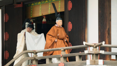 Emperor Akihito, right, leaves after a ritual to report his abdication at the Imperial Palace in Tokyo on Tuesday.