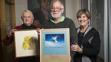 Jane Brummitt, left, and Geoff and Amanda Turville with their rare paintings.