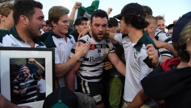 Emotion-charged: Sam Ward is surrounded by teammates after Warringah win the Shute Shield final last year.