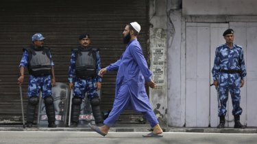 An Indian Muslim man walks past Indian paramilitary soldiers after offering prayer during Eid al-Adha, or the Feast of the Sacrifice, in Jammu, India, on Monday.