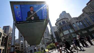 People pass by a TV screen broadcasting President Xi Jinping's opening speech, outside a shopping mall in Beijing. Xi promised to set high standards for China's Belt and Road infrastructure initiative, seeking to dispel claims that it is just a cloak for strategic expansion.