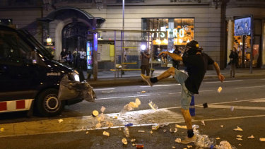 A protester throws rubbish at a police van during clashes in Barcelona.