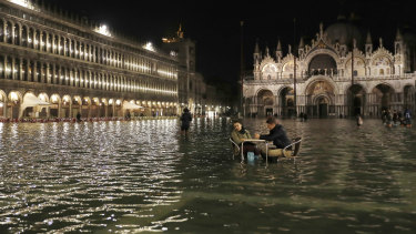 Rising seas: People sit in a flooded St Mark's Square in Venice, Italy, as high tides inundated the city in March 2018.