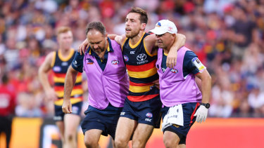 Richard Douglas is helped off the field during the round one match between Adelaide and Hawthorn.