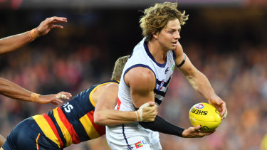 Block and tackle: Hugh Greenwood gets to grips with Fremantle captain Nat Fyfe.