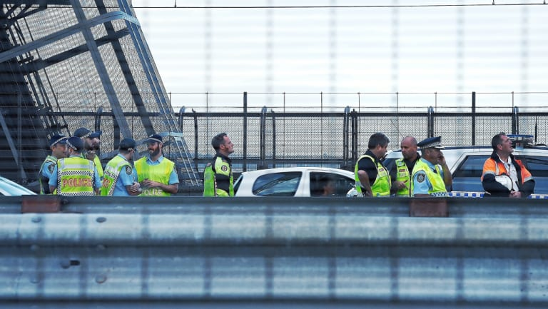 Penalty: Police watch a man climbing Sydney Harbour Bridge, the fine for which will be increased.