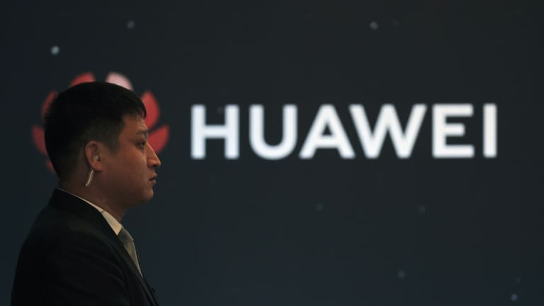 In this January 9 photo, a security guard stands near the Huawei company logo during a new product launching event in Beijing.