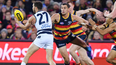 Adelaide skipper Taylor Walker pressures Sam Menegola.