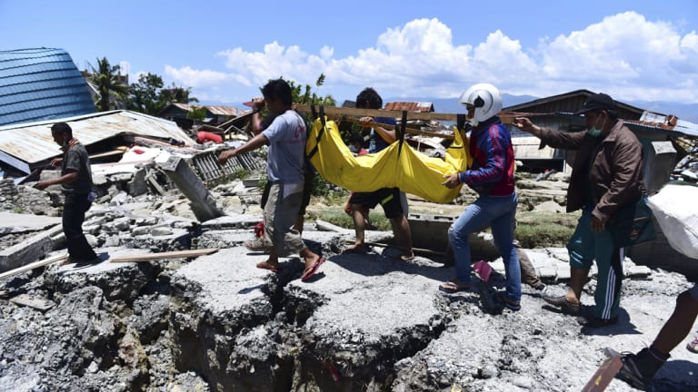 Villagers carry the body of a victim following the earthquake and tsunami in Palu, central Sulawesi.