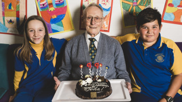Rat of Tobruk John Fleming celebrates his 99th birthday on Friday with Giralang Primary School captains Selima Macadam and Shae Pressley, both 11.