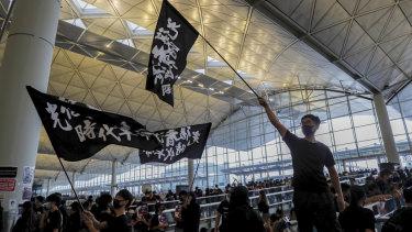 Protesters wave flags at Hong Kong International Airport.