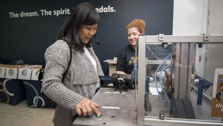 Nhan Nguyen from Sydney with legends and events co-ordinator, Claire Wiscombe, using the mobile press at the Ratbags and Rascals Roadshow Reveal at the Royal Australian Mint.