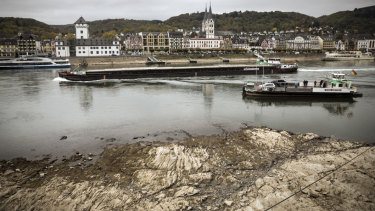 A freighter and ferry pass near rocks visible on the Rhine in Boppard, Germany.