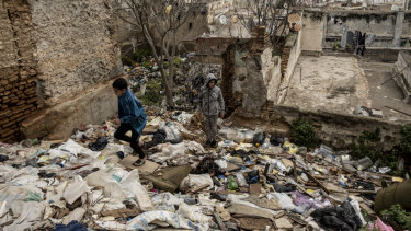 Teenagers climb over rubbish in a vacant lot in the Casbah district of Algiers.