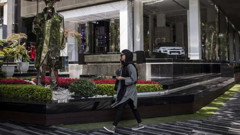 A woman passes by a showroom selling foreign cars in Tehran. Big European companiesare weighing whether to rapidly end operations in Iran in line with US sanctions.