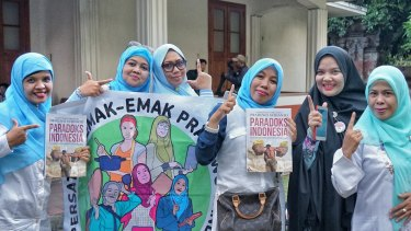Some of Prabowo's Emak - emak (mothers) volunteers proudly posing  with the 'V' sign while holding up his latest book after the event in Bali on Friday.