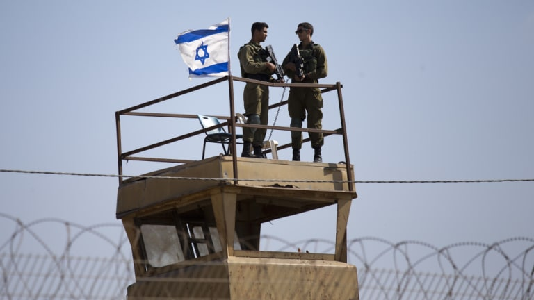 Israeli soldiers keep watch over the Israel-Gaza Strip border, where almost 60 Palestinians were shot and killed and 1360 injured this week.