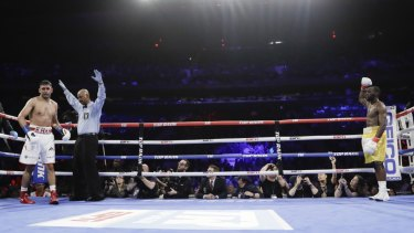 Over and out: The referee stops the fight during the sixth round when Amir Khan could not continue after a low blow by Terence Crawford.