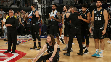 Blow out: Shattered Melbourne players and coach Dean Vickerman (far left) after their loss to new title holders Perth in game four of the NBL grand final series.