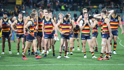 The Crows players leave the field after being beaten by the Pies.