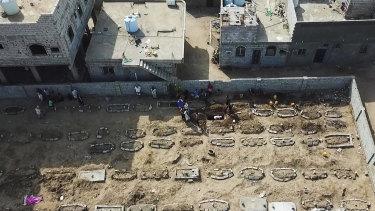 Grave diggers bury bodies at Radwan Cemetery in Aden, Yemen.