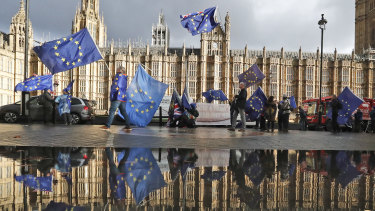 Protesters are reflected in a puddle as they wave European Union flags to demonstrate against Brexit in front of Parliament in London on Monday.
