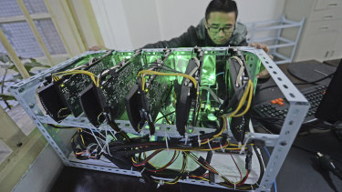 A staff member checks a bitcoin mining computer at the bitcoin mining company Landminers in southwestern China's Chongqing Municipality.
