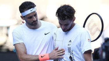 Grigor Dimitrov consoles Dominic Thiem at the net after their fourth-round clash.