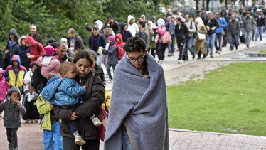 Migrants walk from the main station in Dortmund, Germany, to a reception hall on arrival in 2015.