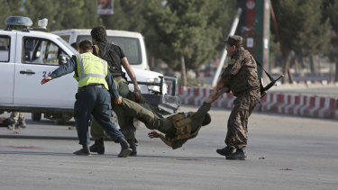 Afghan security personnel carry an injured officer after an attack near the Kabul Airport, in Kabul, Afghanistan on July 22.