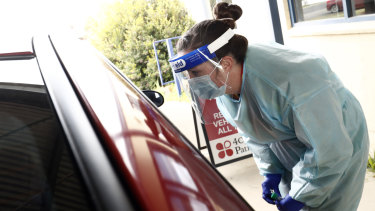 Medical professionals perform COVID testing at a drive-through clinic.