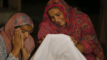 Women mourn beside the dead body of their family member Sabir Hussain, who died after their house collapsed after a powerful earthquake in Sahang Kikri, northeast Pakistan