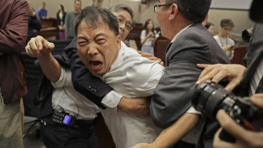 Pro-democracy lawmaker Wu Chi-Wai is restrained at the Legislative Council in May.