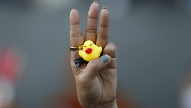 The three-finger protest gesture is flashed by a protester while holding a yellow duck, which has become a  symbol of resistance.