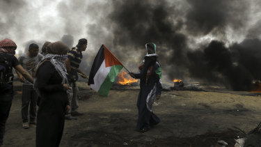 Palestinian protesters burn tyres as a woman waves their national flag near the fence during a protest at the Gaza Strip's border with Israel.