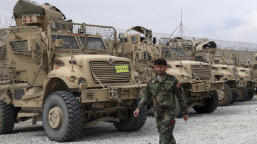 An Afghan soldier walks past vehicles left by the American military.