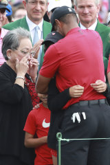 Tiger Woods embraces his daughter Sam and son Charlie, as his mother Kultida wipes away tears.