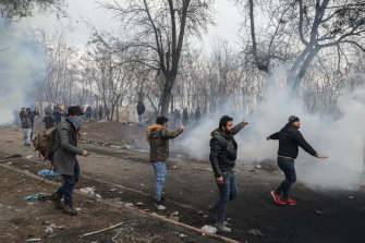 Refugees and migrants shelter from tear gas fired from Greek border guards at the Pazarkule border as they attempt to enter Greece from Turkey.