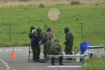 Military officers are disinfected near an airport in Bilbao in northern Spain.