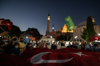 People wave flags and chant slogans after the evening prayers outside Istanbul's famous Hagia Sophia on after the court decision in Istanbul, Turkey.